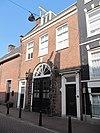 foto van Koetshuis met gevel onder rechte lijst en inrijdeuren in geblokte bakstenen omlijsting