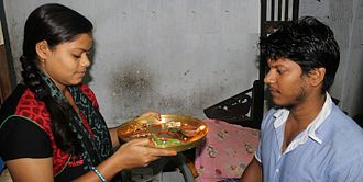 Raksha Bandhan - A sister facing her brother, and holding a tray with rakhis.