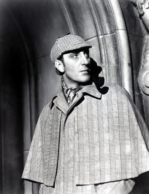 A black and white picture of Sherlock Holmes standing in a cape and deerstalker outside a house