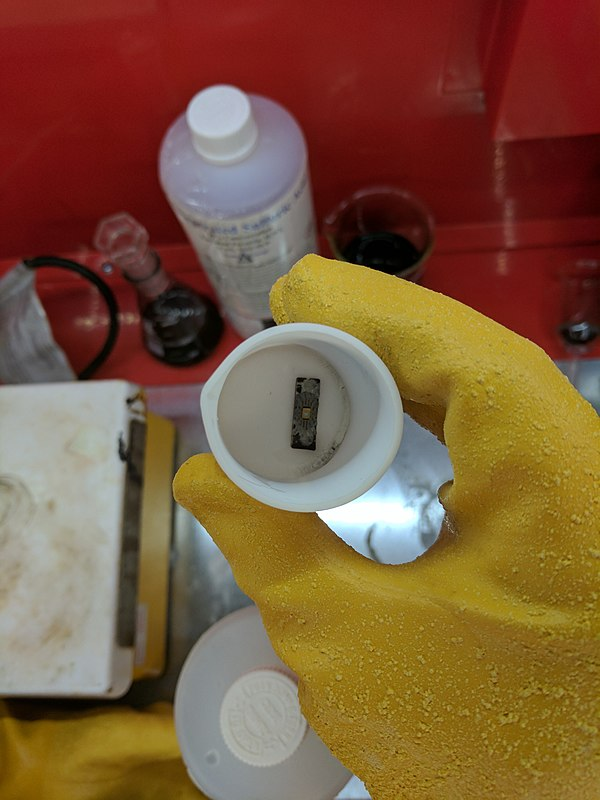 Removing the metal layer from an integrated circuit using a solution of 6 parts 3% hydrogen peroxide to one part 32% hydrochloric acid in a small teflon beaker.