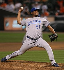 A brown-skinned man with a goatee wearing a gray baseball uniform with blue trim and a blue baseball cap throwing a baseball with his right hand