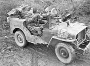 two men in a machine gun armed jeep