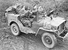 two men in a machine gun armed jeep