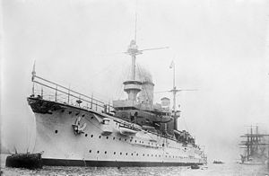 A large white warship bristling with guns sits in harbor; a tall sailing ship lies further aft in the background
