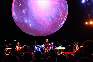 The Smashing Pumpkins perform on a stage with a large orb with projections. From left to right: Nicole Fiorentino, Billy Corgan, and Jeff Schroeder.