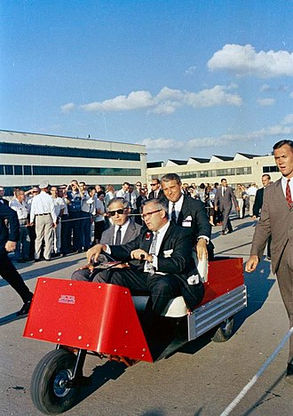 Polaris Sales Agreement - The Director of the George C. Marshall Space Flight Center, Wernher von Braun, rides in the back of a motorized cart with the Chief Scientific Adviser to the Ministry of Defence of Great Britain, Sir Solly Zuckerman in the front passenger seat.