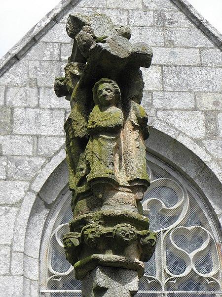 Chapelle Saint-Adrien en Saint-Barthélémy (56). Fontaine-calvaire. Détail. Saint-Jean au pied du Christ en Croix. A l'arrière, remplages de la baie méridionale du croisillon sud.