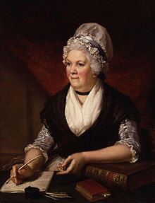 Half-length seated portrait of an elderly woman in 18th-century dress with white lace cap. She is surrounded by books and papers and is holding a quill pen.
