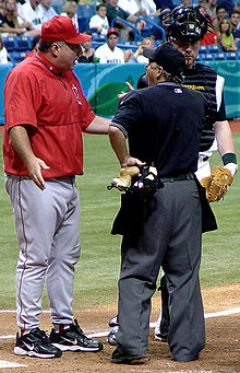 A man in a red warmup with gray pants stands arguing with a man in a black baseball jersey and dark gray pants.