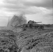 A spinning flail in front of a tank throws dirt into the air
