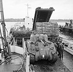 Sherman tanks, a Churchill AVRE with fascine and a Churchill bridgelayer of 79th Armoured Division loaded into a landing craft, Saxmundham-Ipswich area, 28 January 1944. H35473.jpg
