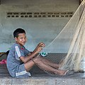 Sitting boy weaving a fishing net in Laos.jpg