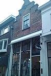 foto van Winkel-/woonhuis met gepleisterde trapgevel bekroond door topmakelaar op kraagsteen met leeuwenmasker