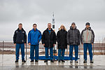 Soyuz TMA-19M crew and backup crew in front of a Soyuz rocket statue.jpg