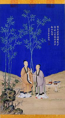 Painted vertical scroll with two men wearing robes standing on a rocky landscape and against a deep-blue sky. A strange-looking stone stands in the left foreground. There are five green bamboos in the background, and a low table with several objects on it is placed on the ground on the right. The man on the left, who is taller and looks older, is giving a long object that might be a tree branch with flowers on it to the man on the right.