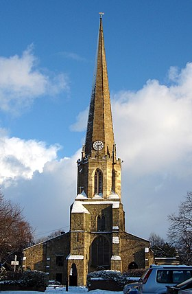 A church, about 50 metres tall, the top half of it a spire with a clock at the base of the spire. The church is lit by sunlight, with some snow on ledges around the tower, and a blue sky with a few clouds behind it