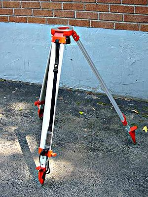 Tripod (surveying) - A surveyor's tripod with a shoulder strap. The head of the tripod supports the instrument while the feet are spiked to anchor the tripod to the ground.