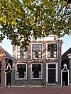 foto van Pand met verdieping, omlijste ingang en vijf zesruitsvensters onder zadeldak met voorschild en topschoorsteen