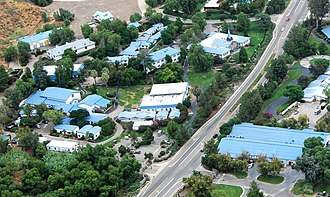 The Hole (Scientology) - Aerial view of the Hole (the white-roofed building in the center of the photo). The maintenance garage, where makeshift showers were set up for the confined executives, is visible at the bottom right across the road