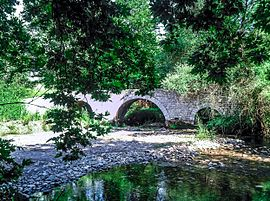The three arches stone bridge of Paos River near Dafni