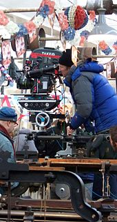 A man wrapped in a blue jacket and black hat looks down the scope of a large film camera. There is red, white, and blue bunting hanging overhead.