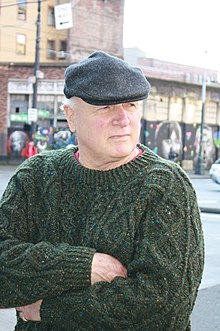 a pale elderly man in a sweater and flat cap