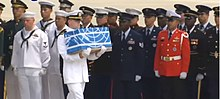 A soldier carries a cermonial box past other soldiers