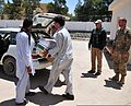 U.S. Army Lt. Col. Christopher Miller, officer in charge, Special Operation Forces District Team-Afghanistan, watches an Afghan family load fabrics and sewing machines into a car at Firebase Thomas, Afghanistan 110704-A-UB106-751.jpg