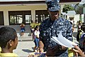 U.S. Navy Machinist's Mate Fireman Bobby G. Moore, assigned to the amphibious transport dock ship USS Denver (LPD 9), signs autographs for children during a cultural exchange community service program Aug. 28 130828-N-KL846-539.jpg