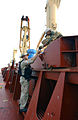 US Navy 021206-N-0331L-006 assisting a crewmember of a Thai merchant ship in opening the cargo bay for inspection.jpg