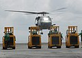 US Navy 030413-N-8794V-001 An SH-60F Seahawk from Helicopter Anti-Submarine Warfare Squadron Four (HS 4) takes off while Sailors man forklifts while waiting for cargo during a vertical replenishment.jpg