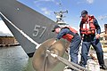 US Navy 040423-N-3228G-009 Seaman Jesse L. Miller, left, and Seaman Stephen Hopwood install a rat guard on a bow mooring line.jpg