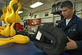 US Navy 050613-N-1332Y-064 Aircrew Survival Equipmentman Airman Rodolfo Inzunza of Rio Rico, Ariz., inspects a life preserver for air leaks in the Paraloft Shop aboard the conventionally powered aircraft carrier USS Kitty Hawk.jpg