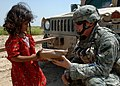 US Navy 060603-N-6901L-154 Spc. Christopher Starr from the 1st Special Troops Battalion, 1st Brigade Combat Team, 4th Infantry Division, gives part of a meal-ready-to-eat (MRE) to a six-year-old Iraqi girl in Husiniyah, Iraq.jpg
