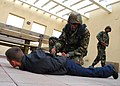 US Navy 090227-N-4044H-019 Master-at-Arms 3rd Class Kawaun Thomas detains a suspect during a team-building obstacle course at Naval Support Activity Naples.jpg
