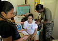US Navy 090420-A-0759M-035 Lt. Helen Cann, Battalion Surgeon assigned to Health Service Support Platoon, examines a child at Umiray Elementary School during a joint medical civic action project supporting Balikatan 2009 in Ding.jpg