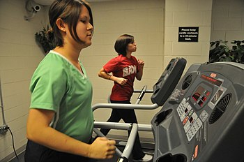 US Navy 090831-N-2541H-003 Lt. Cmdr. Monica Leutgendorf and Hospital Corpsman 3rd Class Teresa Arnold exercise at the medical center gym