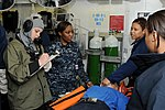 US Navy 091201-N-5049H-094 Culinary Specialist Seaman Jaydee Wood reports the status of a casualty while Hospital Corpsmen 2nd Class Nakita Byrum and Delita Tolbert practice medical procedures during a general quarters drill.jpg