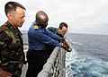 US Navy 100212-N-6676S-006 Lt. Brandon Le nd Aerographer's Mate 2nd Class Cory Clare look on as Nigerian navy Cmdr. Godffrey Kwetishe gathers sea surface temperature reading.jpg