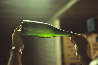 Traditional method - A bottle of undisgorged Champagne resting on the lees. The yeast used in the second fermentation is still in the bottle, which is closed with a crown cap.