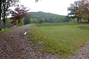 Battle of Fort Davidson - One side of Fort Davidson as seen today. The crater from the powder magazine blast is visible on the far right. Pilot Knob is the hill at the back.