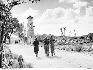 Victoria, Labuan - Australian 9th Division Army jogging through the ruins of Victoria town hall and remains of the clock tower on 26 June 1945 after a heavy bombing from the Allied forces.