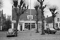 Voorgevel van winkel-woonpand, leibomen en geparkeerde auto's op de voorgrond - Etten-Leur - 20398502 - RCE.jpg