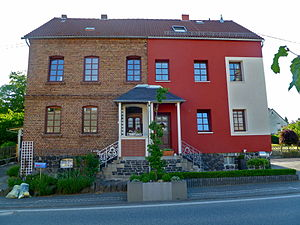 Exterior insulation finishing system - A historic brick building in Germany covered with EIFS on the right side.