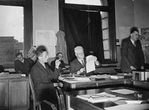Official History of New Zealand in the Second World War 1939–45 - A conference at the War History Branch in relation to the 2NZEF unit histories. Attendees include Chief Archivist Eric McCormick (left foreground, with cigarette) and Editor-in-Chief Major-General Howard Kippenberger (speaking, at right), 5 July 1946