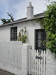 Semi-detached single storey vernacular cottage; full hipped roof with asbestos cement tiles. Facade facing Durban Road: sash windows (12 panes) and louvred shutters; double leafed modern stock French door; intrusive unpainted modern garage door; Type of site: House Current use: House.