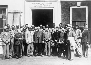 A group of men gathered outside a large building