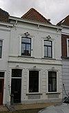 foto van Huis onder schilddak en met grijsgepleisterde lijstgevel, waarin segmentvormig overtoogde vensters met kuiven in stucwerk