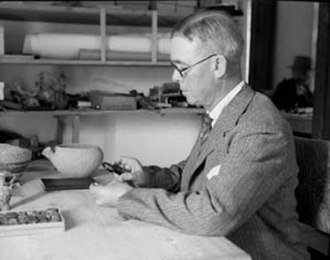 William F. Badè - William F. Badè examining an artifact, circa 1933