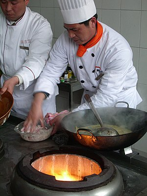 Chefs cooking with a wok in China. Preparing f...